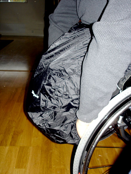 Backpack on wheelchair with rain cover on