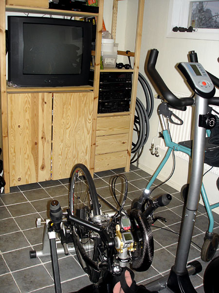 The user's arm cycle and his wife's exercise bike in front of TV in exercise room