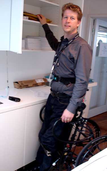 User in standing wheelchair, retrieving envelope from upper shelves in paper supply closet