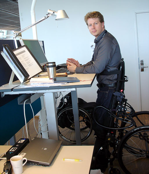 User in standing wheelchair at desk