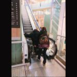 Ride up an escalator in a wheelchair with assistance