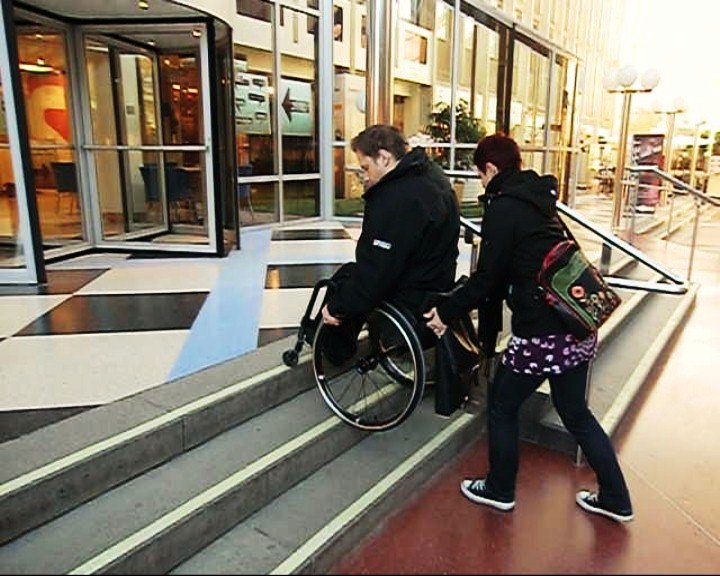 Go down a flight of stairs with a wheelchair with assistance