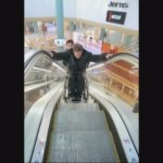 Ride down an escalator in a wheelchair with assistance