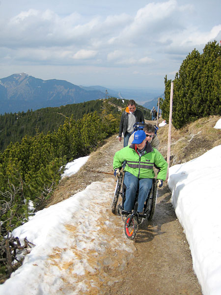 User with off-road chair on a mountain trail