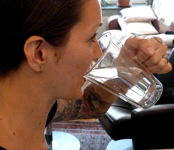User drinks coffee from her insulated glass mug