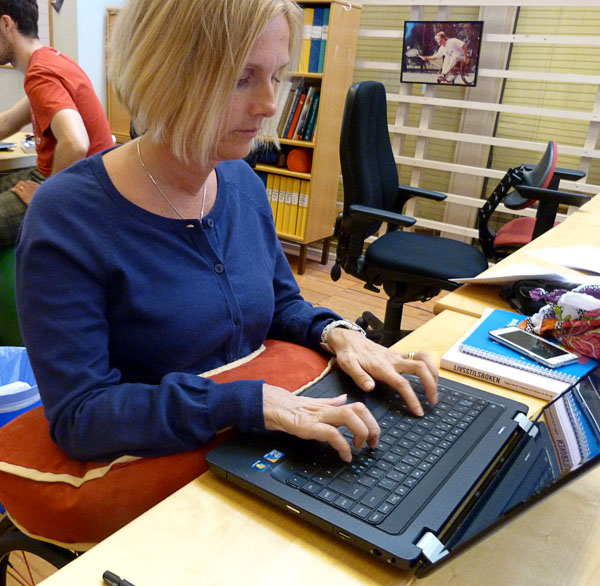 User with her laptop. Forearms resting on support cushion