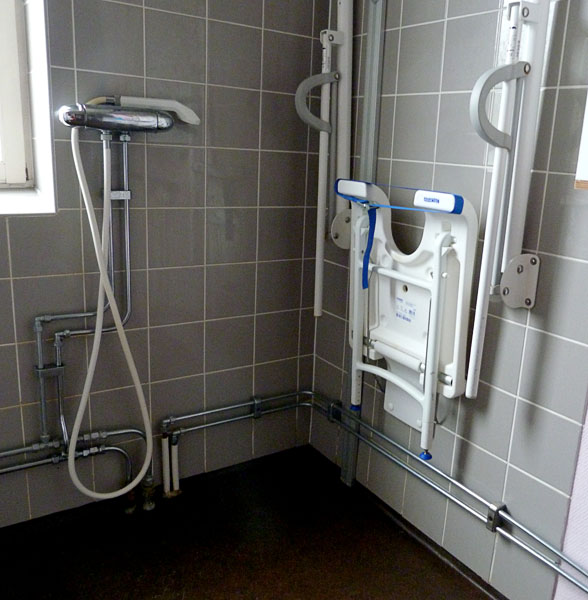 Adapted wall-mounted shower stool, folded up against the wall