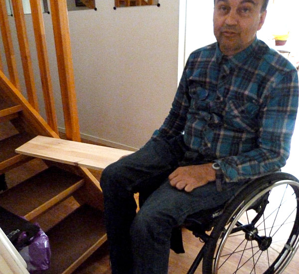 User has transferred from stairs to wheelchair using sliding board