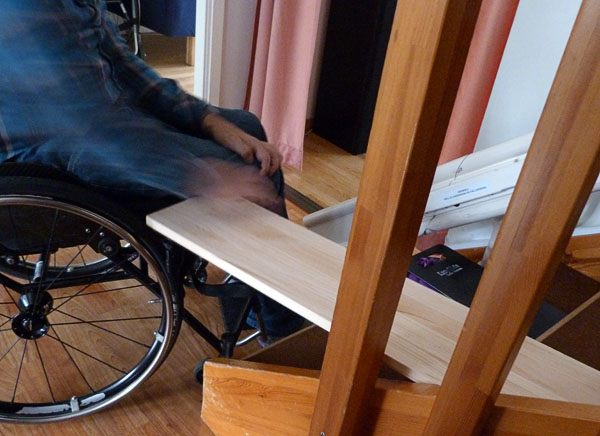 Sliding board between stairway and wheelchair