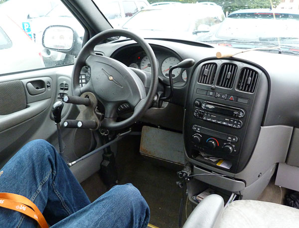 User in driver's seat with modified steering wheel