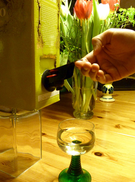 Easy handle on boxed wine; user taps wine by pushing the handle up