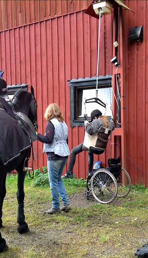 User transfers from wheelchair to horse using a lift