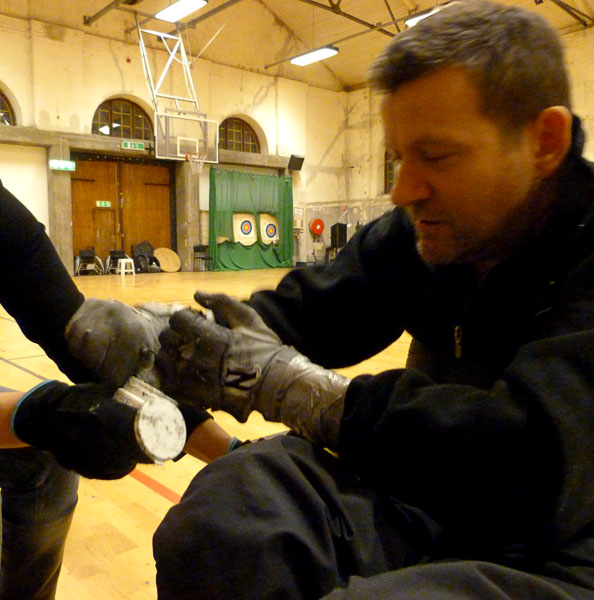 User gets assistance applying handball glue to glove