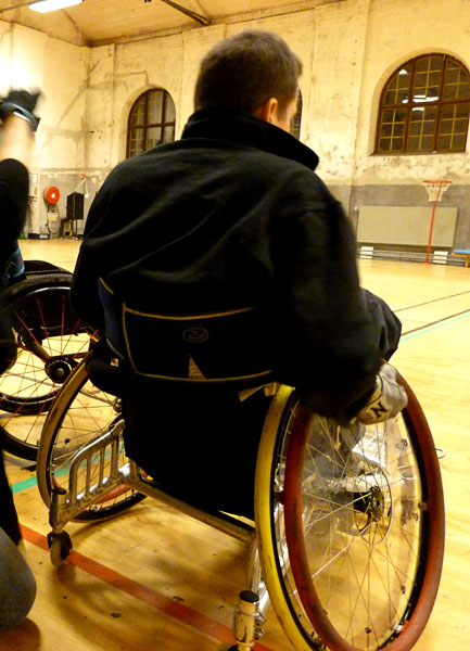 User with soft corset attached around back of wheelchair