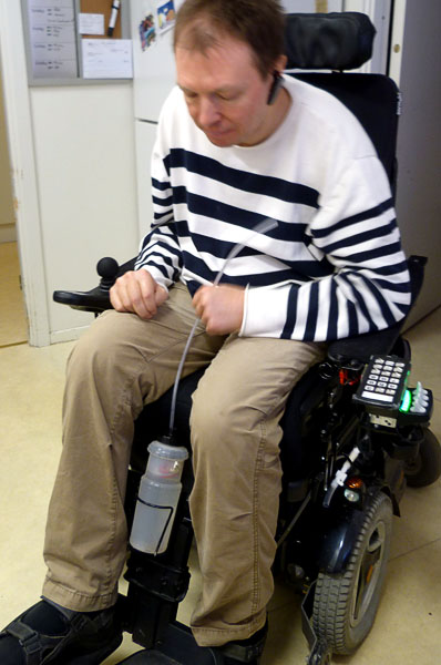 User with water bottle attached to wheelchair