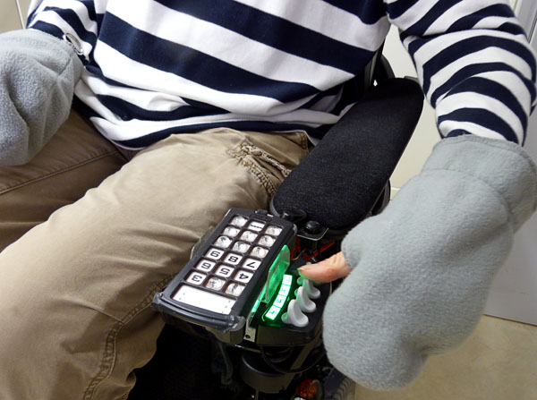 User operates wheelchair while wearing custom-made mitten