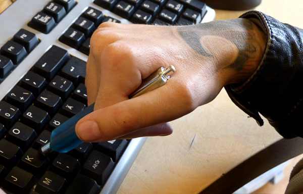 User holds stylus with her right hand (pen rests between index and middle fingers and in the webbing between the thumb and index finger)