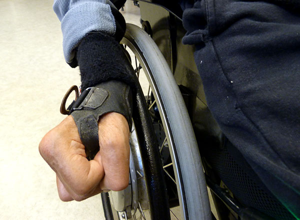 Wrist strap to facilitate soft braking of the wheelchair