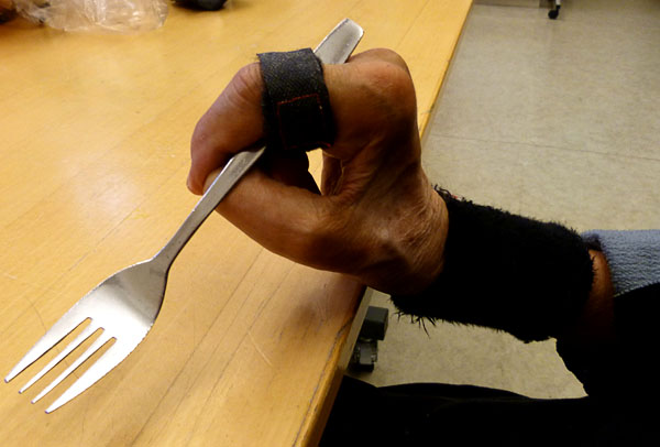 User holds the fork using the flatware strap
