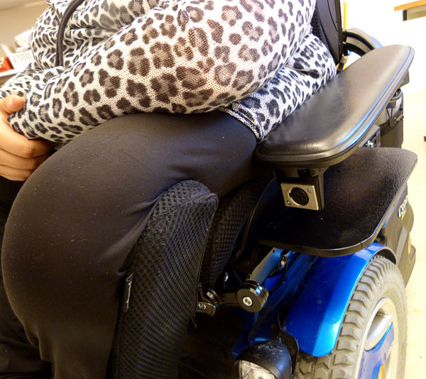 The user sitting in the wheelchair modified with built-in sliding board and removable leg support