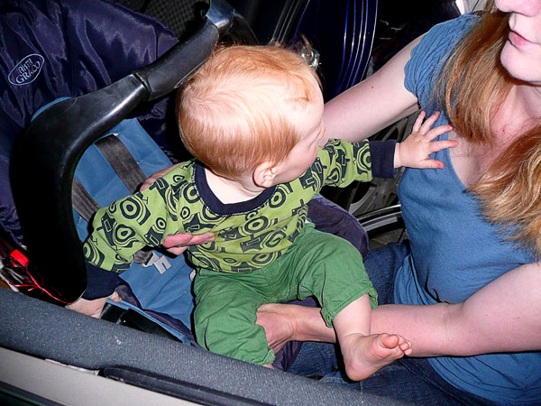 The parent pushes the child over to the car seat