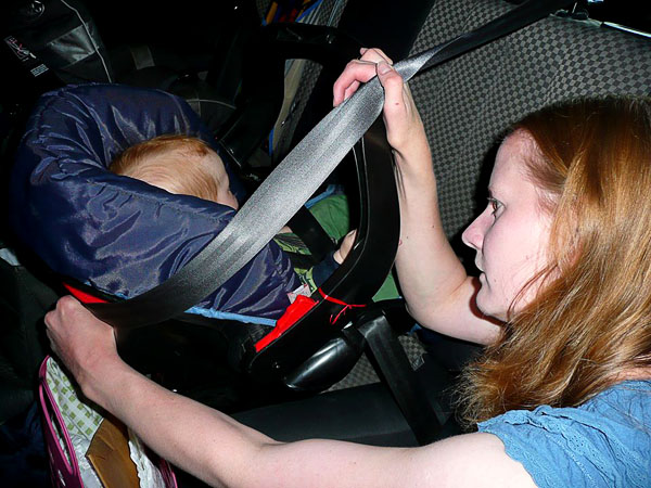 The parent pulls out the belt to maximum length and pulls it around the infant seat