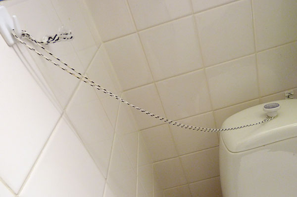 String attached to the knob of the toilet and on the wall