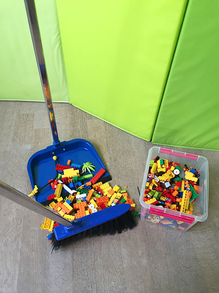 The user sweeps up Lego with a broom. Photo from mammapappalam.se