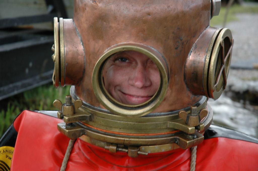 Användaren i närbild med dykarhjälmen på, han ler.