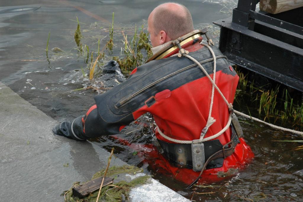 Användaren med dykardräkt på väg ner till vatten. Han har nedre ringen av dykarhjälmen på.